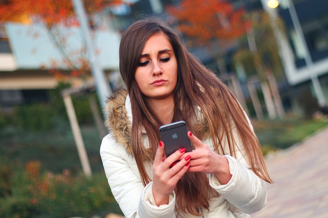 Girl walking outside and using an iPhone
